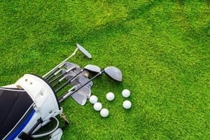 a golf bag and balls in the grass